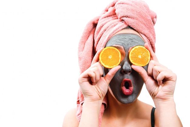 Masker voor huid vrouw, blij en grappig meisje maakt masker voor gezichtshuid, meisje sluit haar ogen met oranje, geïsoleerde foto, emotionele geslachtsrol