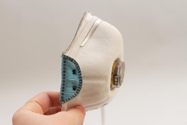 Maskerademhalingsmasker voor gezicht houdt in hand op een witte achtergrond