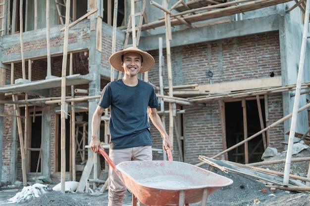 Mason glimlach terwijl het duwen van kruiwagen met woningbouw achtergrond