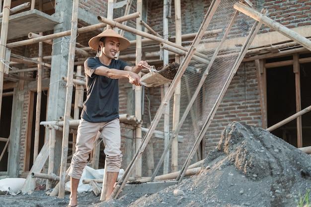 Mason houdt schop vast terwijl hij zand draagt om te zeven tegen de achtergrond van de woningbouw