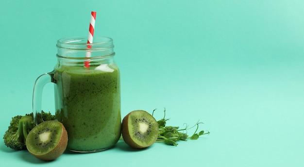 Mason jar met groene smoothie en ingrediënten op munt achtergrond