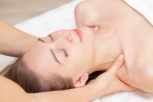 Massage en lichaamsverzorging. spa lichaam massage vrouw handen behandeling. vrouw die massage in de kuuroordsalon hebben voor mooi meisje