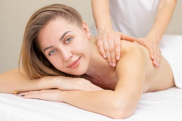 Massage en lichaamsverzorging. spa lichaam massage vrouw handen behandeling. vrouw die massage in de kuuroordsalon hebben voor mooie vrouw