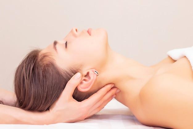 Massage en strekken van de cervicale spieren. het mooie meisje krijgt massage in een kuuroordsalon. lichte tinten foto's. reuma, artrose