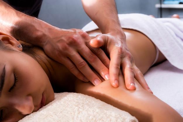 Massage is een prachtige foto. een mooie vrouw ligt in het kantoor van de massagetherapeut. foto's van spabehandelingen.