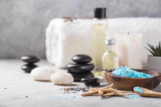 Massage olie fles aroma essentiële en natuurlijke geur zout met stenen, kaarsen op betonnen grijze tafel.