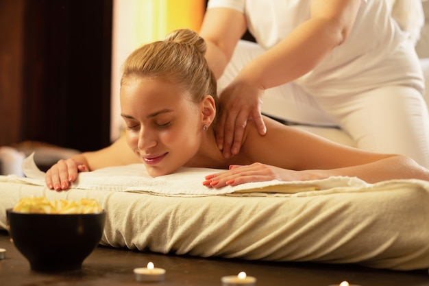 Massage sessie. glimlachende blonde vrouw met vastgebonden haar die tevreden is met de vaardigheden van massagemeester in salon