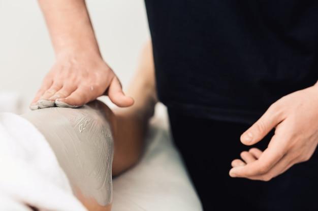 Massage van benen met blauwe klei in spa. cosmetische kliniek, spa, wellnesscentrum, gezondheidszorgconcept.