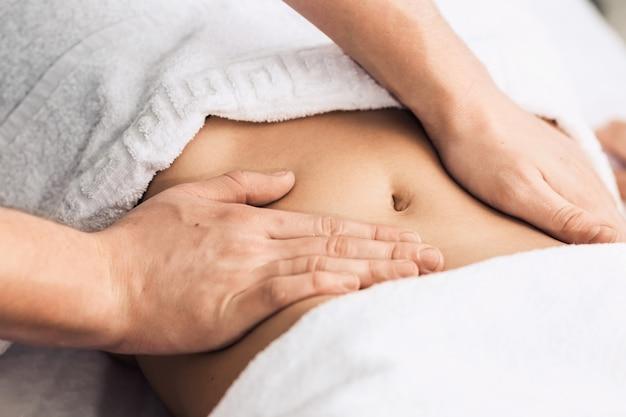 Massage van de maag in de spa. cosmetische kliniek, spa, wellnesscentrum, gezondheidszorgconcept.