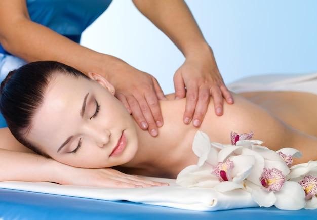 Massage van schouder voor jonge mooie vrouw in horizontale kuuroordsalon -
