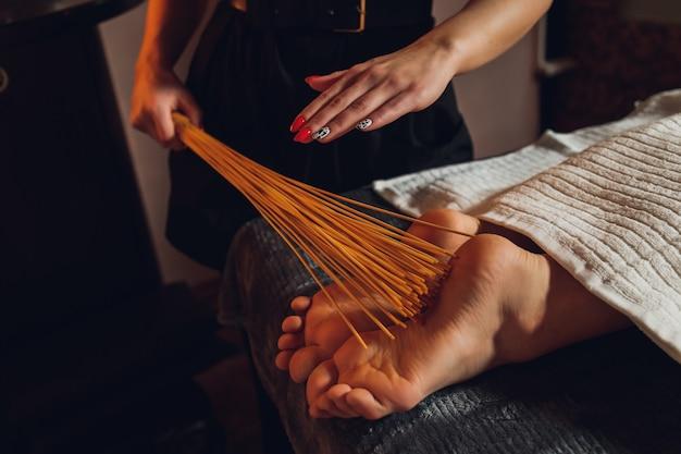 Massage van vrouwelijke voeten met bamboestokken