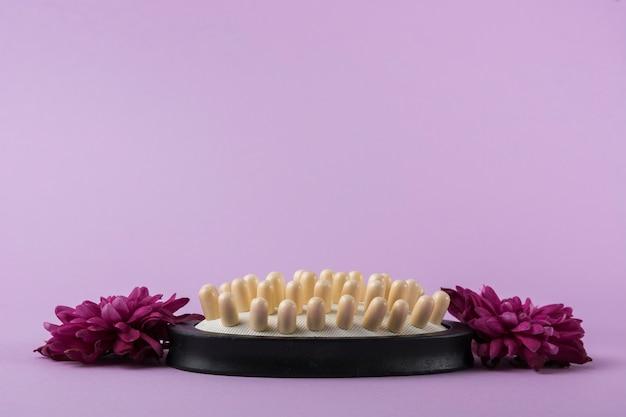 Massageborstel met roze bloemen tegen purpere achtergrond