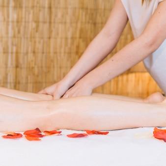 Massageconcept met bloemen naast vrouw