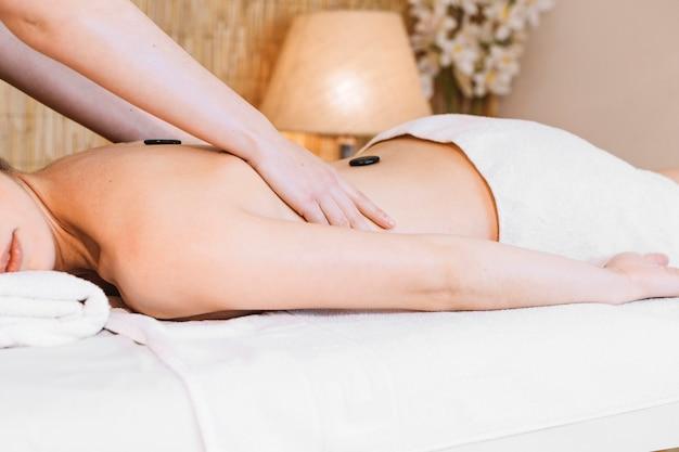 Massageconcept met stenen op de rug van de vrouw