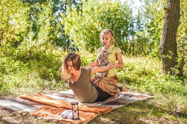 Massagemeisje implementeert haar massagevaardigheden op de grond.