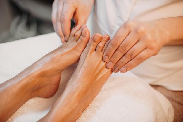 Massageprocedure voor voeten en tenen uitgevoerd door een professionele spa-medewerker in de salon
