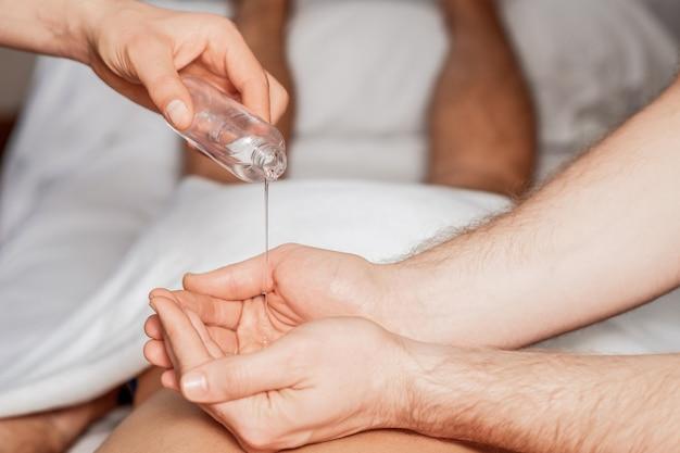 Massager giet olie op handpalmen tijdens rugmassage van de vrouw.