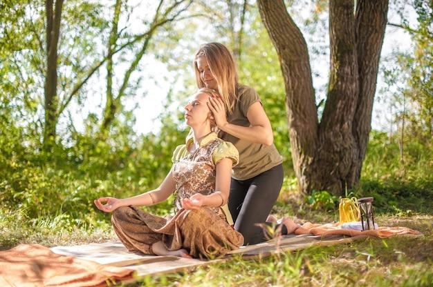 Massagespecialist masseert een meisje grondig in de rustige buitenlucht.