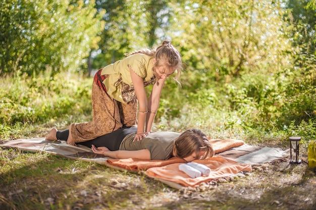 Massagespecialist voert een geweldige massage adequaat uit in het bos.