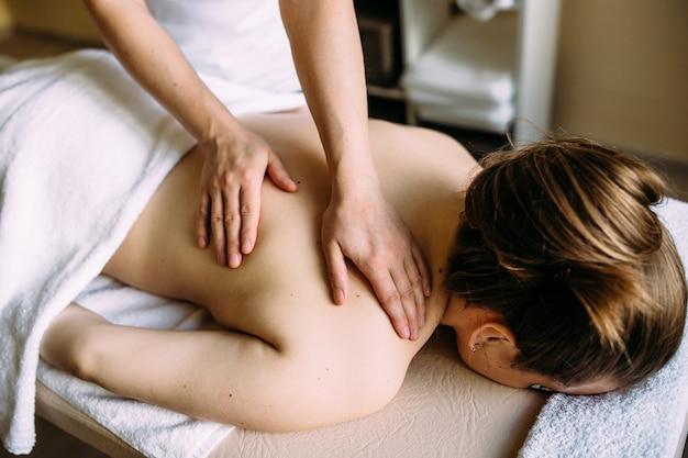 Massagetherapeut doet massage op het vrouwelijk lichaam in de spa