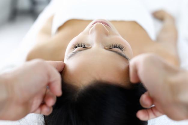 Massagetherapeut geeft hoofdmassage aan vrouw