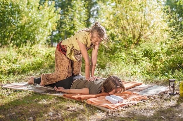 Massagetherapeut masseert een meisje op het gras