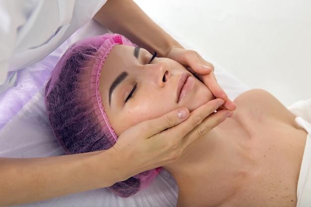 Massagetherapeut schoonheidsspecialist doet massage van de schouders, het meisje liggend op haar rug in de kap