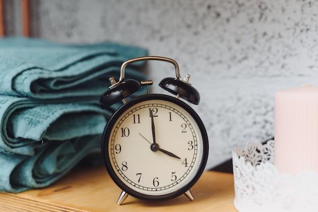 Massagetijd analoge zwarte klok op een plank met blauwe handdoeken en kaarsen. het concept massageartikelen