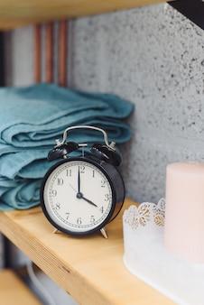 Massagetijd analoge zwarte klok op een plank met blauwe handdoeken en kaarsen. het concept van massageartikelen