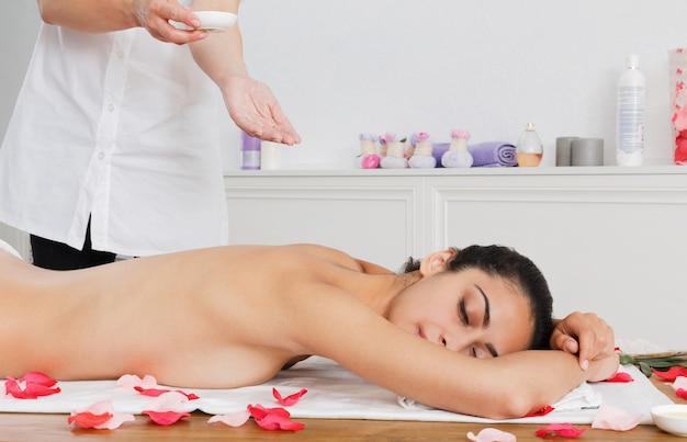 Massagist maakt olie-lichaamsmassage in het wellnesscentrum van de spa
