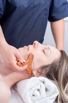 Masseer de nek en het gezicht van het meisje met een natuurlijke houten stimulator, close-up. gezichts- en halsverzorging. lymfedrainage gezichtsmassage met houten stimulator