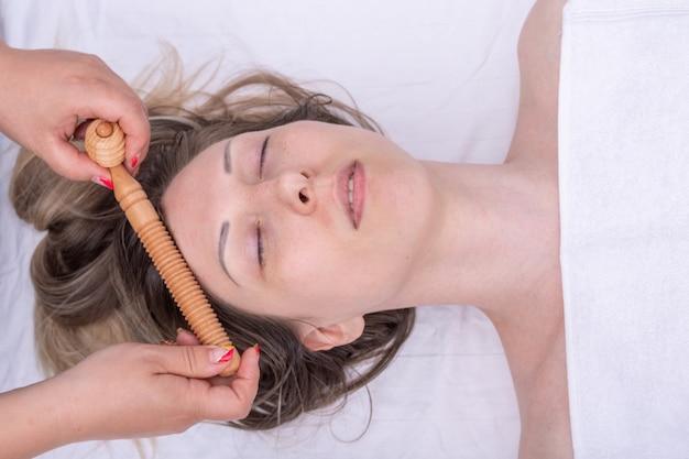 Masseer het gezicht en de haarwortels van het meisje met een houten roller-stimulator, close-up. gezichts- en haarverzorging. lymfedrainage gezichtsmassage, rimpelcorrectie