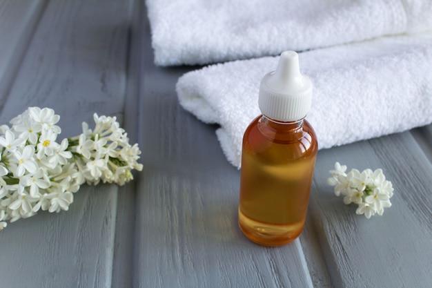 Masseer olie in de glazen fles met bloemen