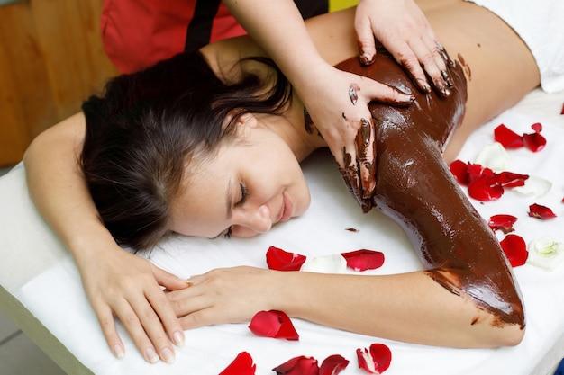 Masseur die chocolade toepast op de rug van de vrouw