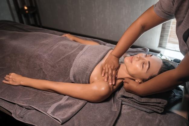 Masseur die massage geeft aan de nek en schouders van de vrouw in de spa