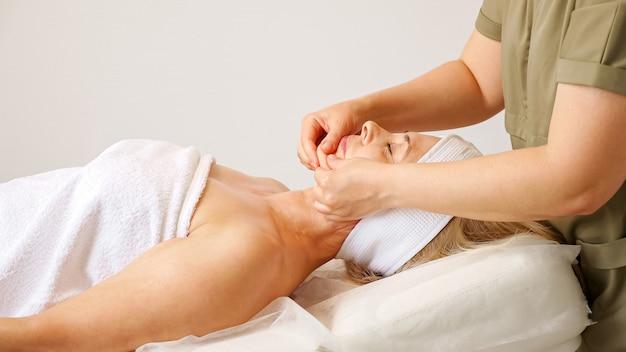 Masseur die nek- en borstmassage doet aan vrouw.