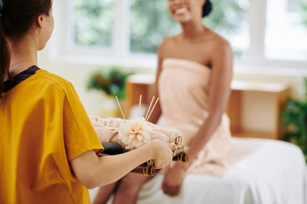 Masseur dienblad met warmgewalste handdoeken naar lachende jonge vrouw zittend op bed in spa salon te brengen
