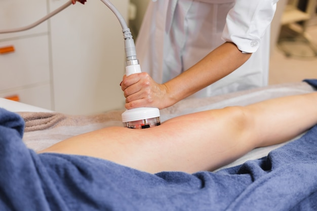 Masseur doet anti-cellulitis massage aan cliënt in de schoonheidssalon van de spa met behulp van olie