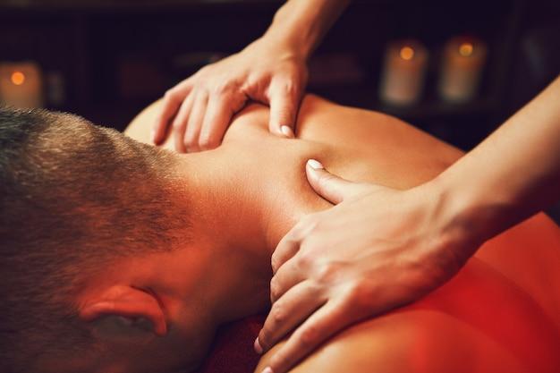 Masseur doet nekmassage op man in de spa salon