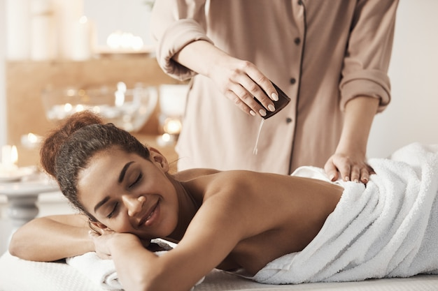 Masseur gietende olie die massage voor mooie afrikaanse vrouw in kuuroordsalon doet.