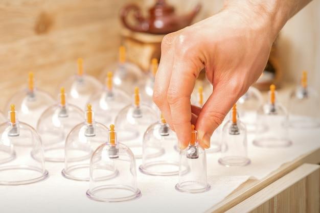 Masseur neemt glazen potten met vacuümmassage met traditionele chinese cupping-therapie van tafel in de spa