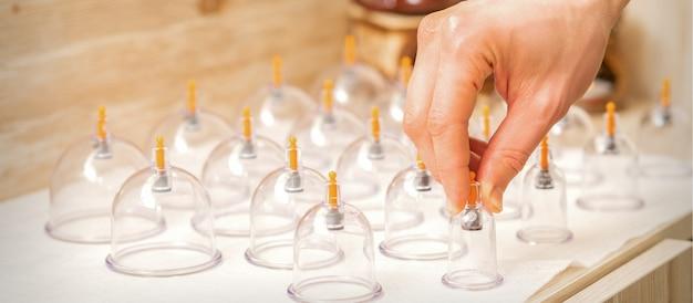 Masseur neemt glazen potten met vacuümmassage van de tafel in de spa