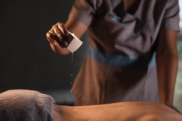 Masseur vrouw druipt wax van een kaars op de rug van een man in spa salon