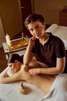 Masseurmeisje die massage doen met vrouw in kuuroordsalon