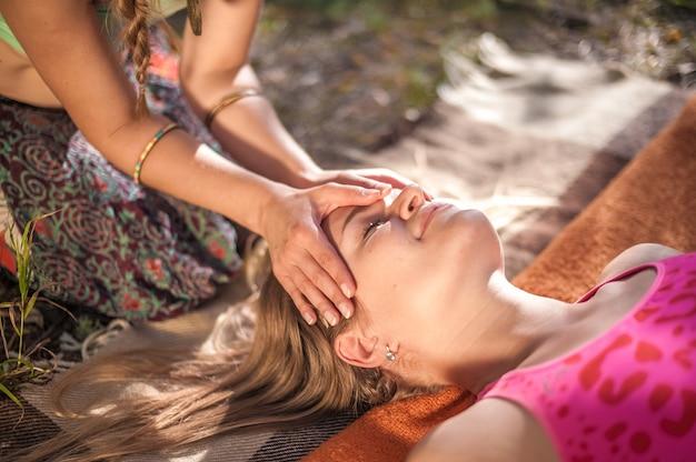 Masseuse die een massage geeft op het gras van het bos.