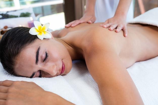 Masseuse die massage geeft om vrouw te ontspannen