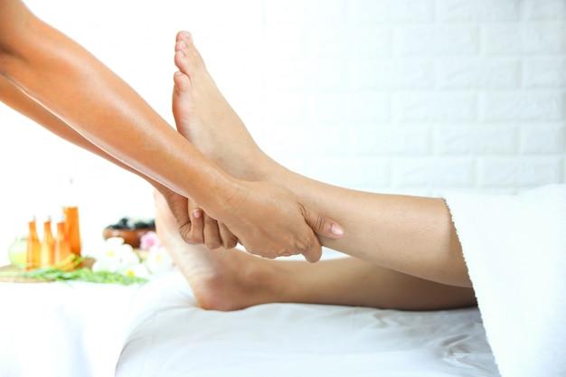 Masseuse gebruikt twee handen tot voetmassage met een jonge vrouw