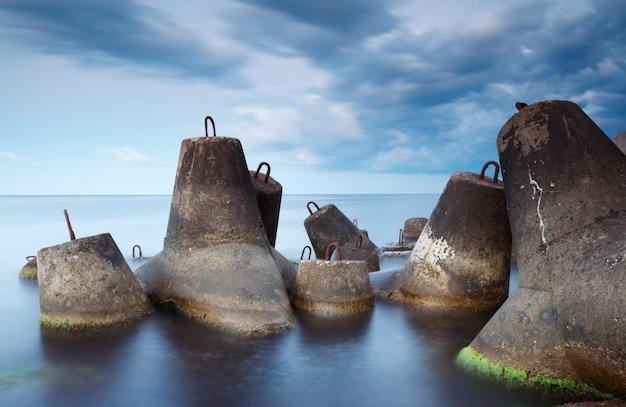 Massieve betonnen tetrapoden vormen een golfbreker met een zacht wazige zee