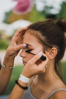 Master class make-up. meisje maakt make-up aan haar vriend