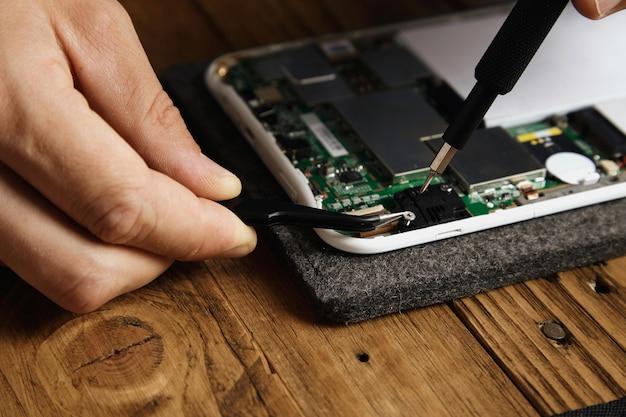 Master gebruikt speciaal gereedschap om het elektronische apparaat zorgvuldig te demonteren. tang en bit-schroevendraaier